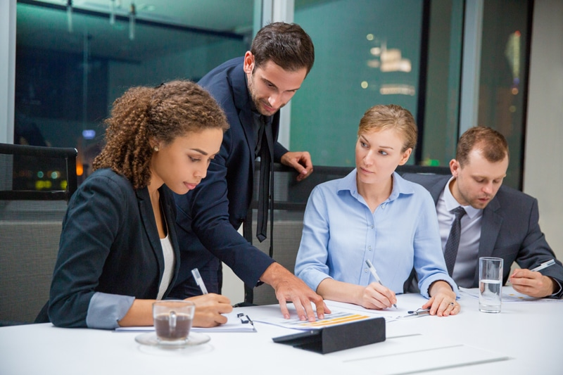 Business management pointing at report in conference room