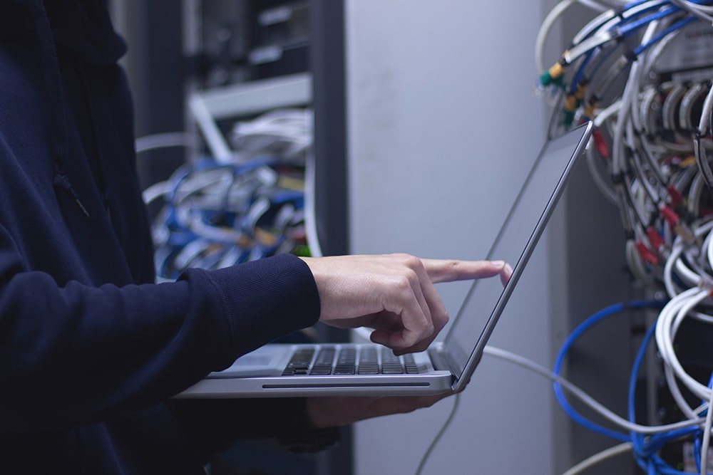 Network system engineer pointing at a laptop
