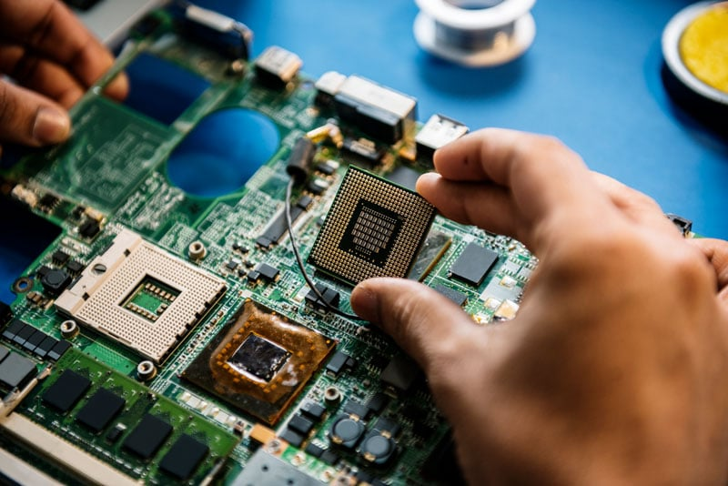 Computer service technician working on motherboard